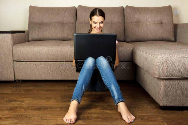 Muchacha bonita que se sienta en piso usando su ordenador portátil en casa en la sala de estar imagenes de archivo