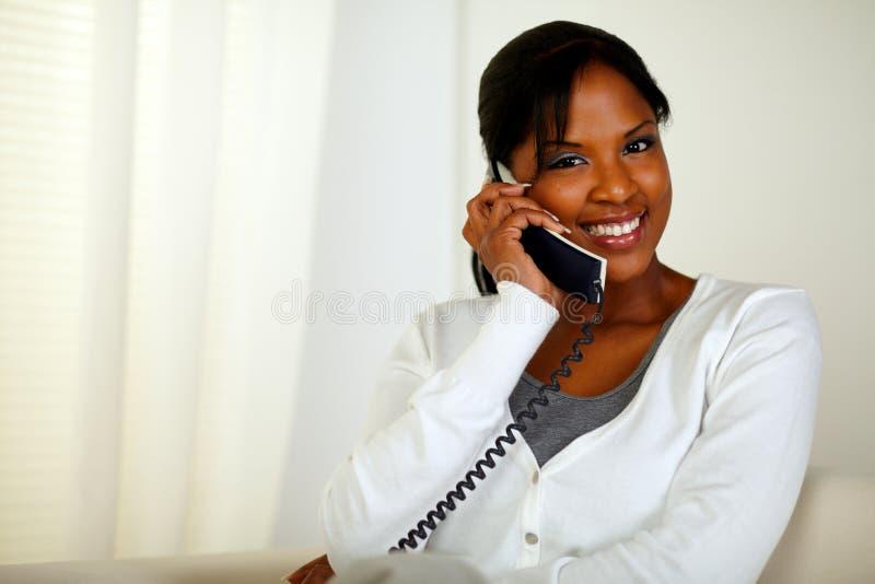 Muchacha bonita que sonríe en usted mientras que habla en el teléfono fotografía de archivo libre de regalías