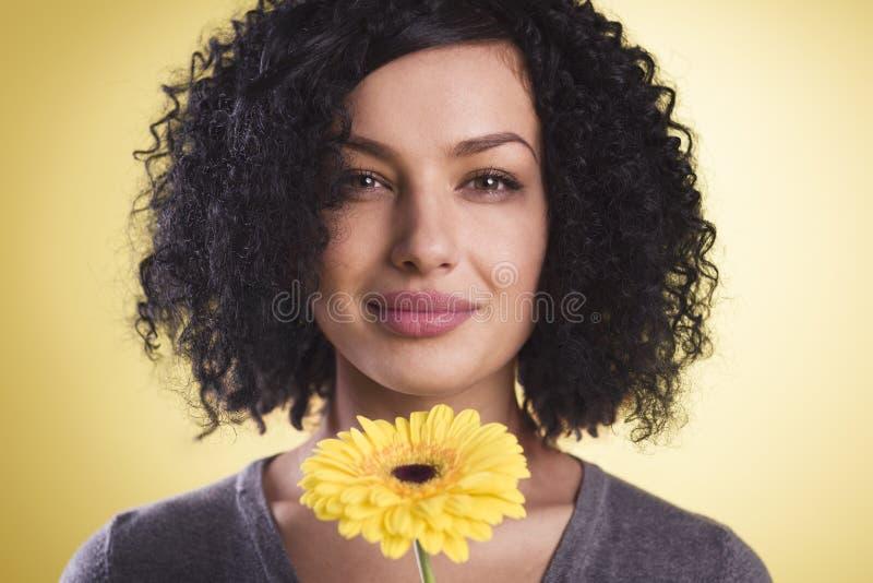 Muchacha bonita que sonríe y que sostiene un flor en su mano foto de archivo libre de regalías