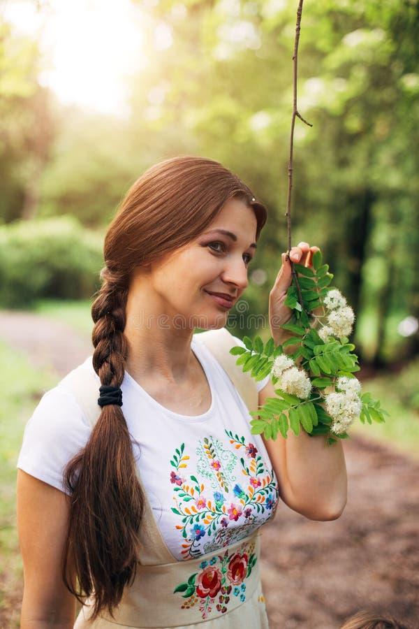 Muchacha bonita sonriente en el vestido ruso con el bordado que lleva a cabo la rama de la rama floreciente del serbal fotografía de archivo libre de regalías