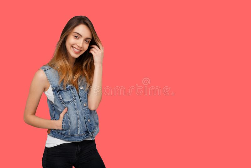 Muchacha bonita sonriente en la ropa casual, presentando en estudio, sobre el fondo coralino Lugar para el texto imagenes de archivo