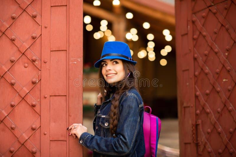 Muchacha bonita sonriente en sombrero azul cerca del edificio viejo con las puertas rojas antiguas Presentaci?n femenina del mode imagenes de archivo