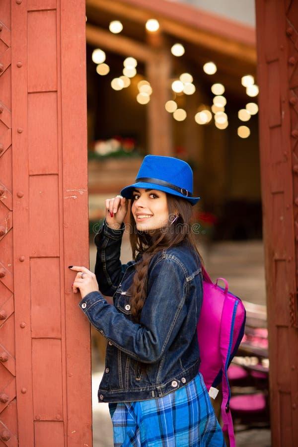 Muchacha bonita sonriente en sombrero azul cerca del edificio viejo con las puertas rojas antiguas Presentaci?n femenina del mode fotografía de archivo
