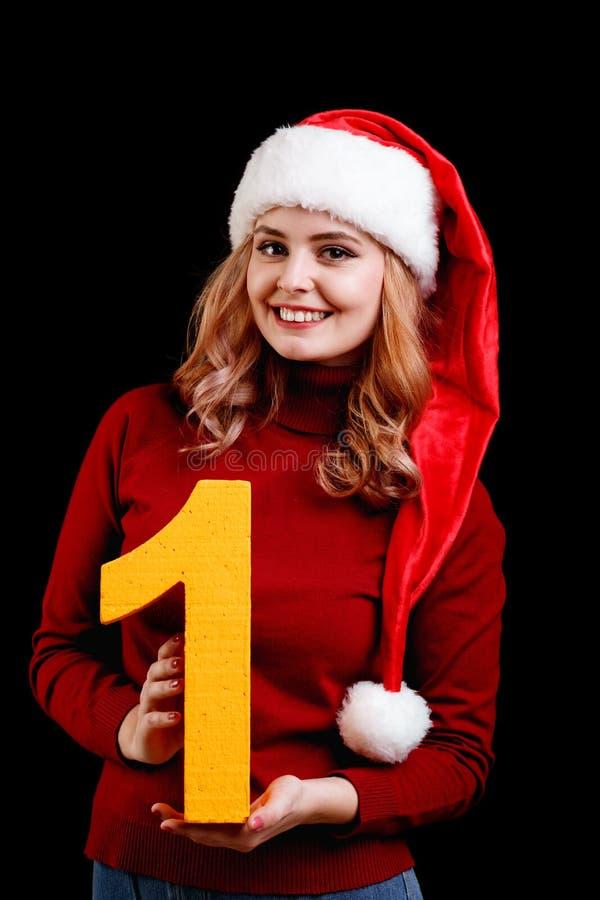 Muchacha bonita sonriente en un sombrero de la Navidad que lleva a cabo el número 1 en un fondo negro Concepto 2018 del Año Nuevo fotografía de archivo libre de regalías