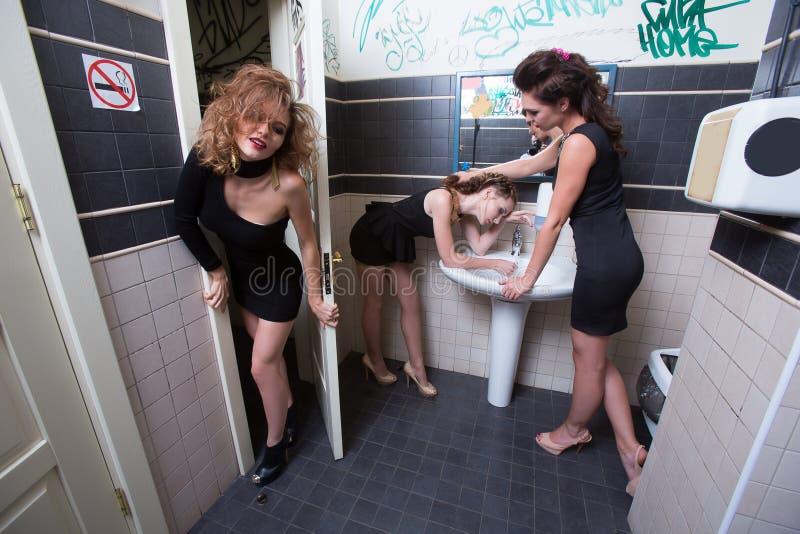 Muchacha borracha en barras del retrete mujeres por la tarde imagen de archivo