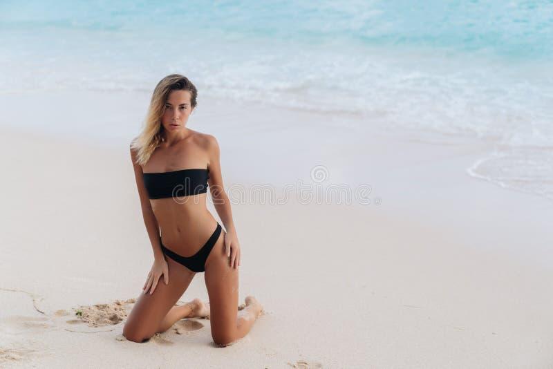Muchacha bronceada atractiva en el traje de baño negro que presenta en la playa arenosa fotos de archivo libres de regalías