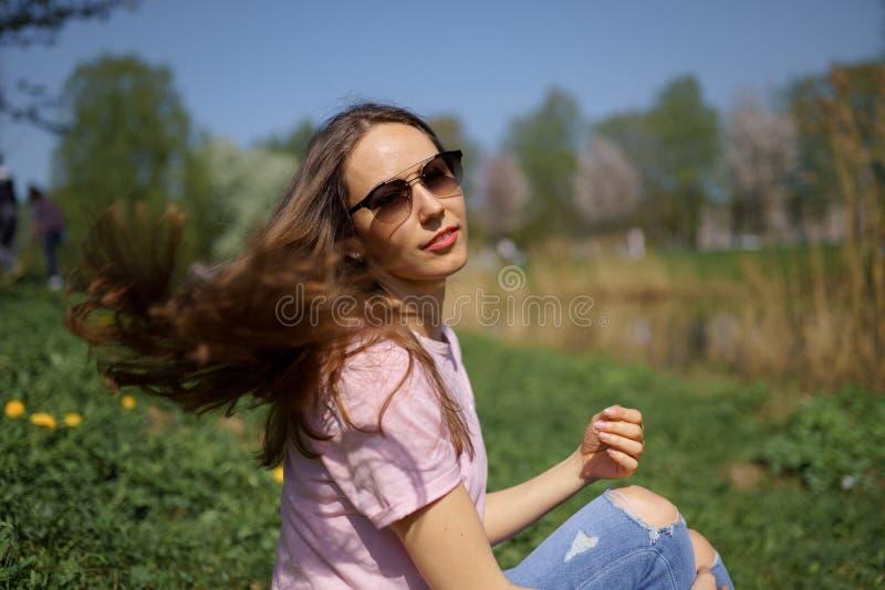 Muchacha cabelluda de la mujer del marr?n feliz joven del viajero que sonr?e y que da vuelta alrededor en un nuevo pa?s de destin imagen de archivo libre de regalías