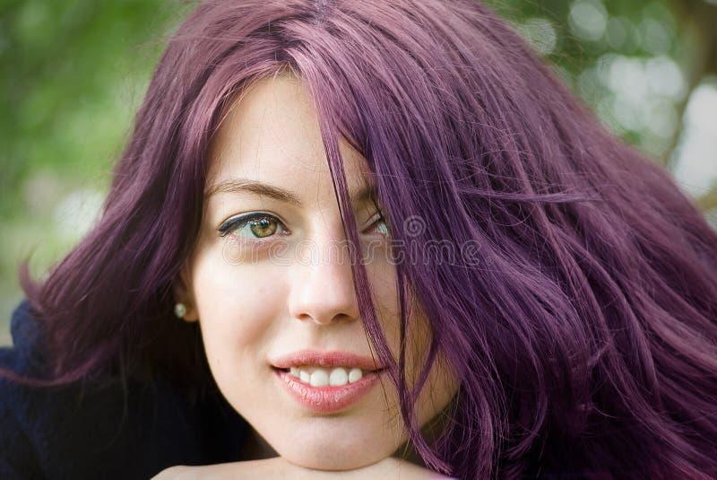 Muchacha cabelluda púrpura con un fondo hojeado verde  imagen de archivo