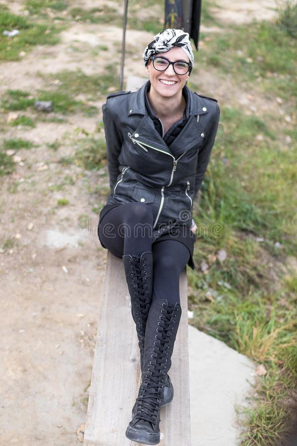Muchacha calva con una bufanda en su cabeza que se sienta en un banco foto de archivo