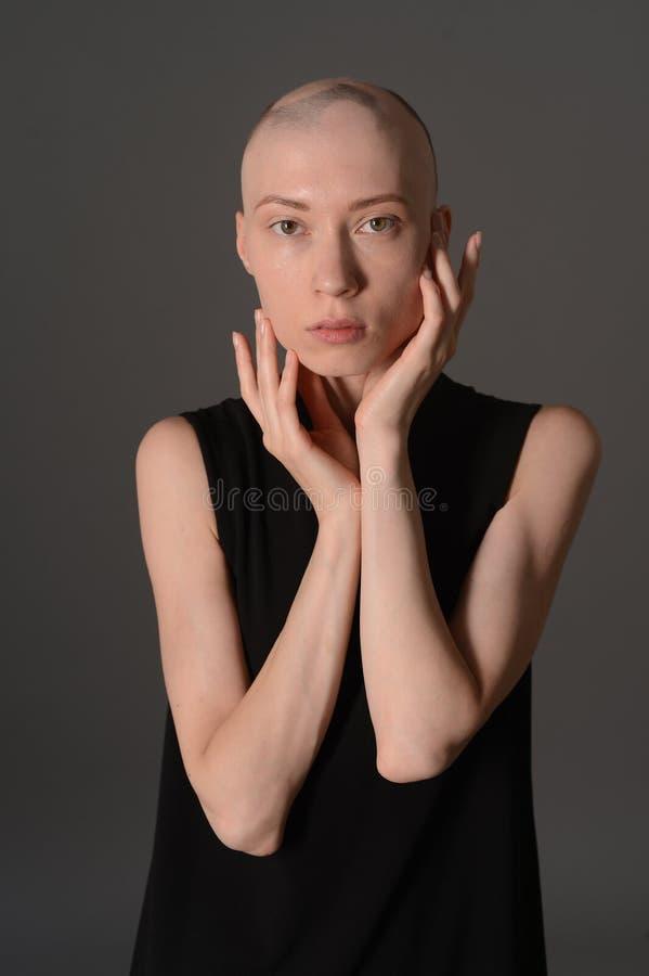Muchacha calva que presenta en estudio en vestido negro imagen de archivo