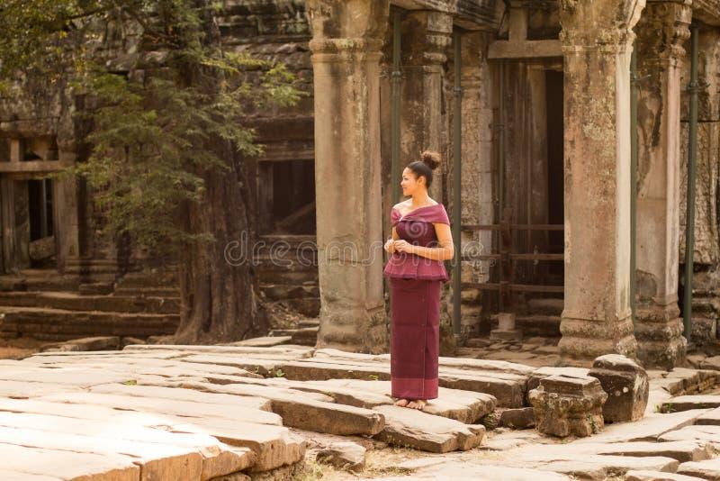 Muchacha camboyana en vestido del Khmer en la entrada al edificio antiguo imagen de archivo libre de regalías