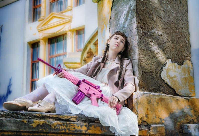 Muchacha cansada con una reclinación rosada del rifle foto de archivo libre de regalías