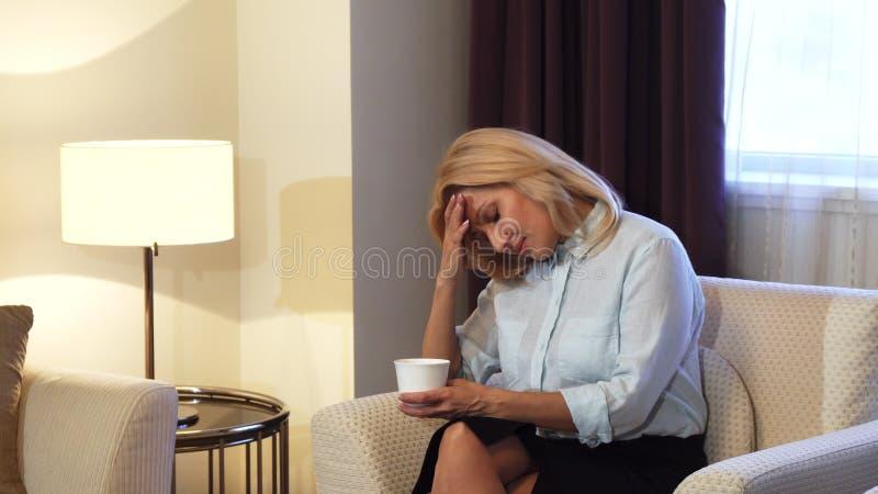 Muchacha cansada que se sienta en silla y el café de consumición imagen de archivo libre de regalías