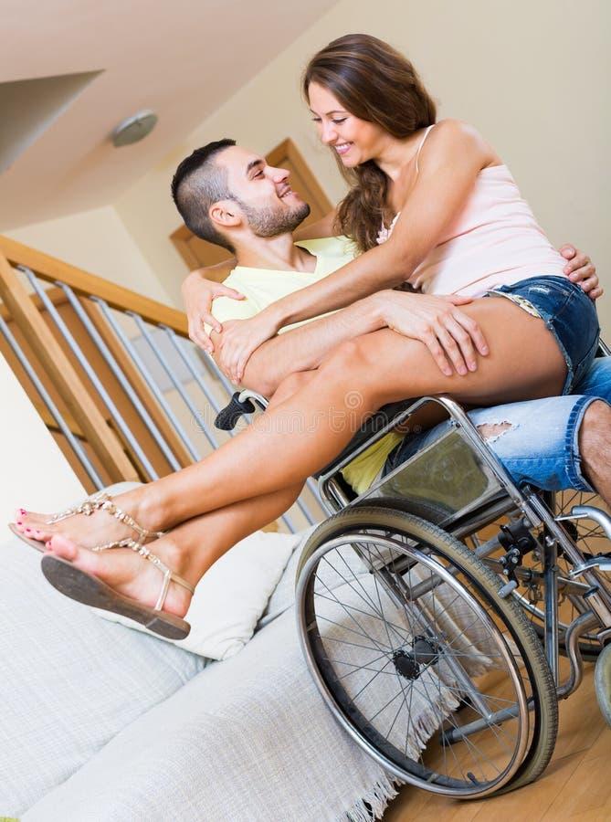 Muchacha cariñosa con su novio en silla de ruedas fotos de archivo libres de regalías