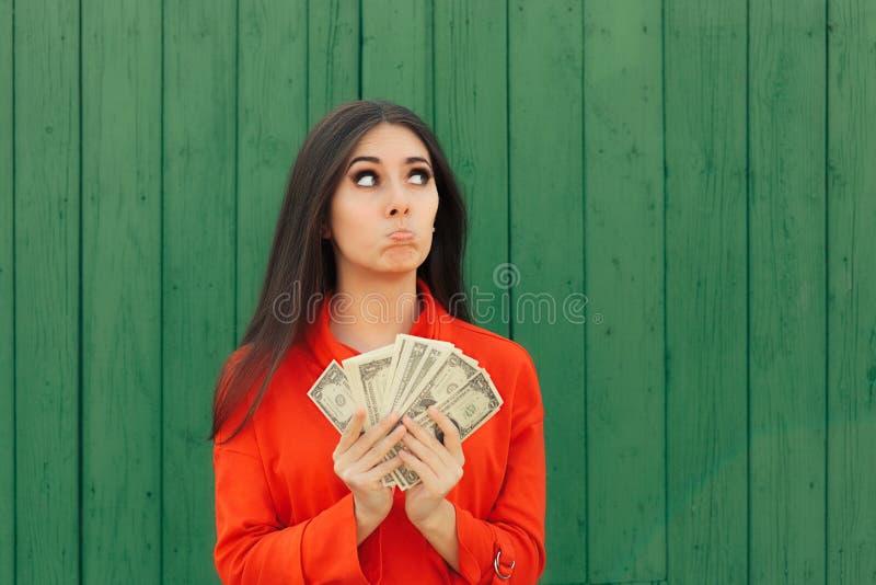 Muchacha casual divertida que sostiene el dinero listo para hacer el pago foto de archivo