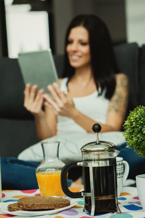 Muchacha casual en casa que toma el desayuno y que lee la tableta foto de archivo