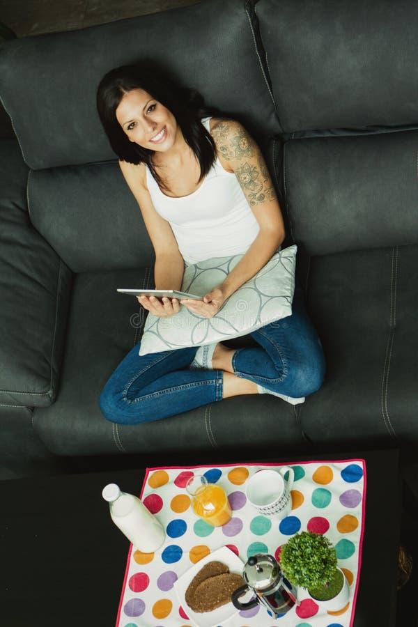 Muchacha casual en casa que toma el desayuno y que lee la tableta imágenes de archivo libres de regalías