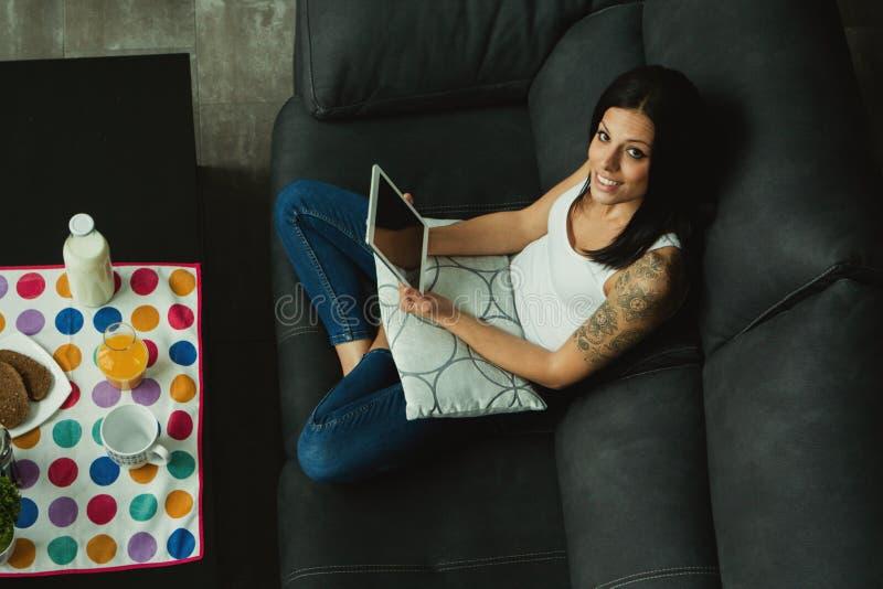 Muchacha casual en casa que toma el desayuno y que lee la tableta imagenes de archivo