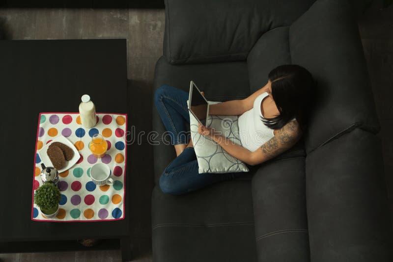 Muchacha casual en casa que toma el desayuno y que lee la tableta imagen de archivo libre de regalías