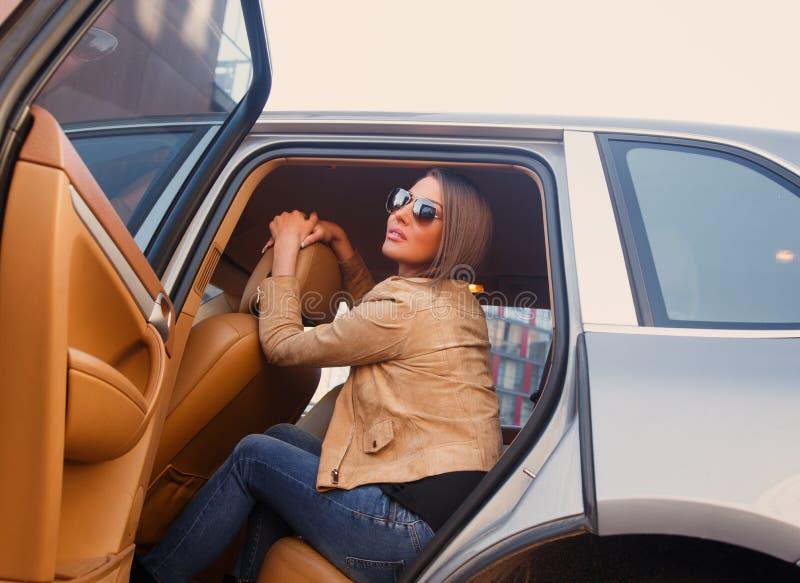 Muchacha casual sonriente en un coche imagenes de archivo