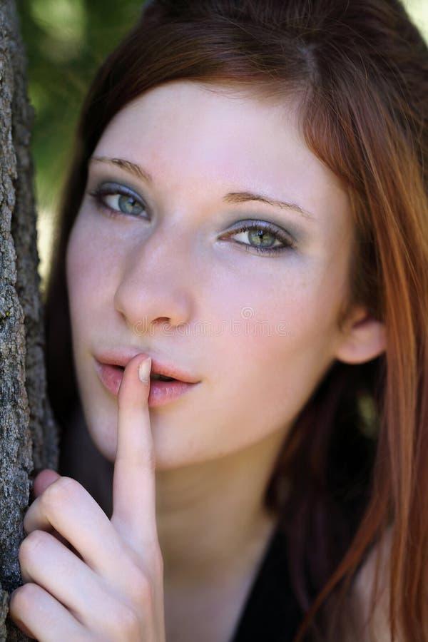 Muchacha caucásica adolescente joven con el dedo a los labios fotografía de archivo