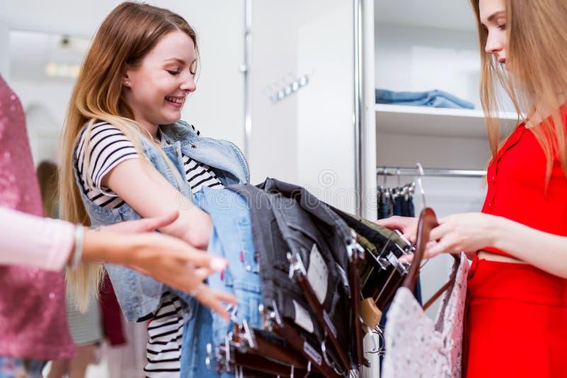 Muchacha caucásica alegre que compra o que elige vaqueros con un ayudante de tienda en una tienda de ropa fotos de archivo