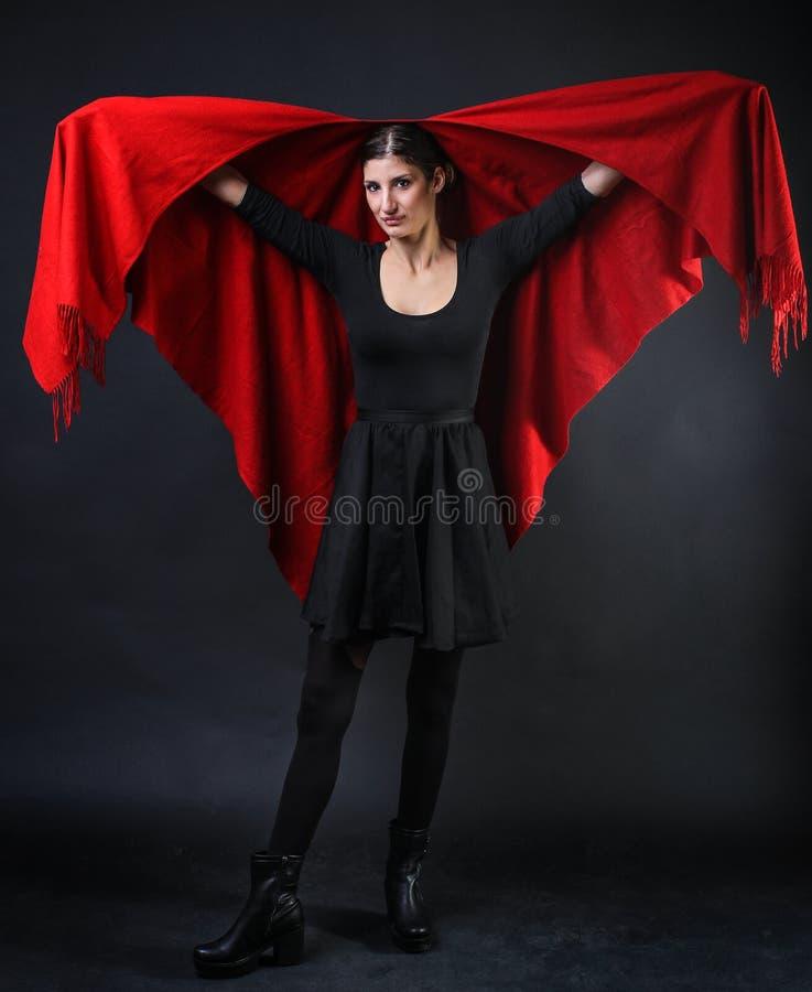 Muchacha caucásica atractiva en un poncho rojo fotos de archivo