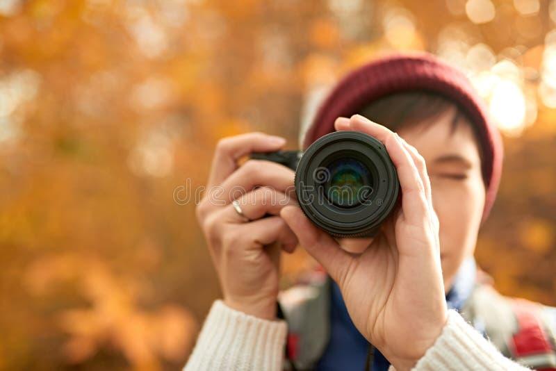 Muchacha caucásica atractiva que toma imágenes con una cámara mirrorless a través del bosque en la caída en Canadá fotos de archivo