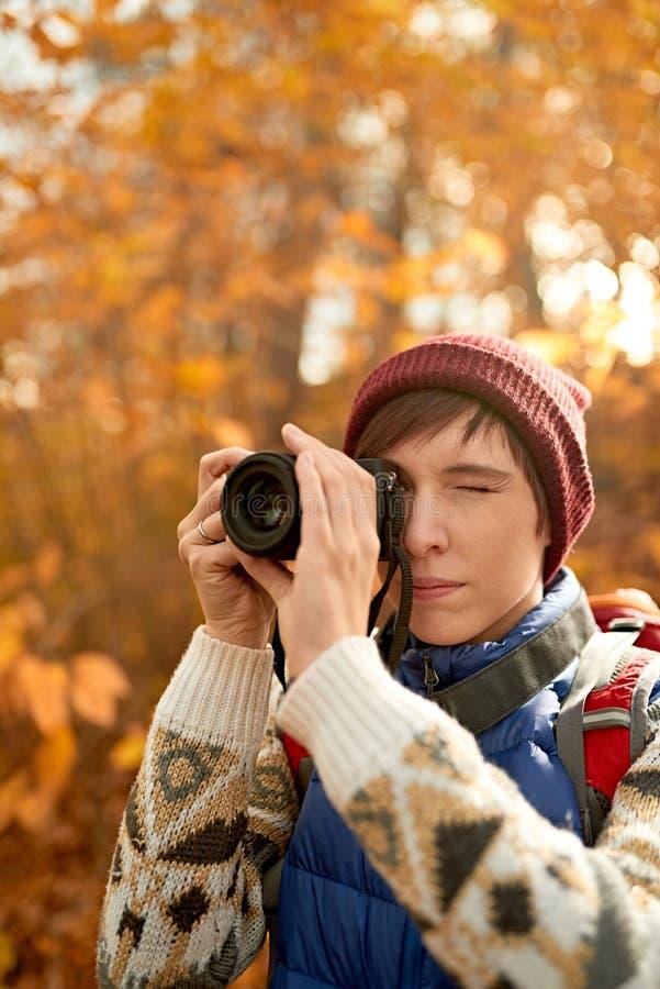 Muchacha caucásica atractiva que toma imágenes con una cámara mirrorless a través del bosque en la caída en Canadá fotografía de archivo libre de regalías