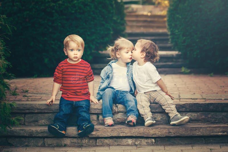 Muchacha caucásica blanca adorable divertida linda de tres de los niños muchachos de los niños que se sienta junto besándose fotos de archivo libres de regalías