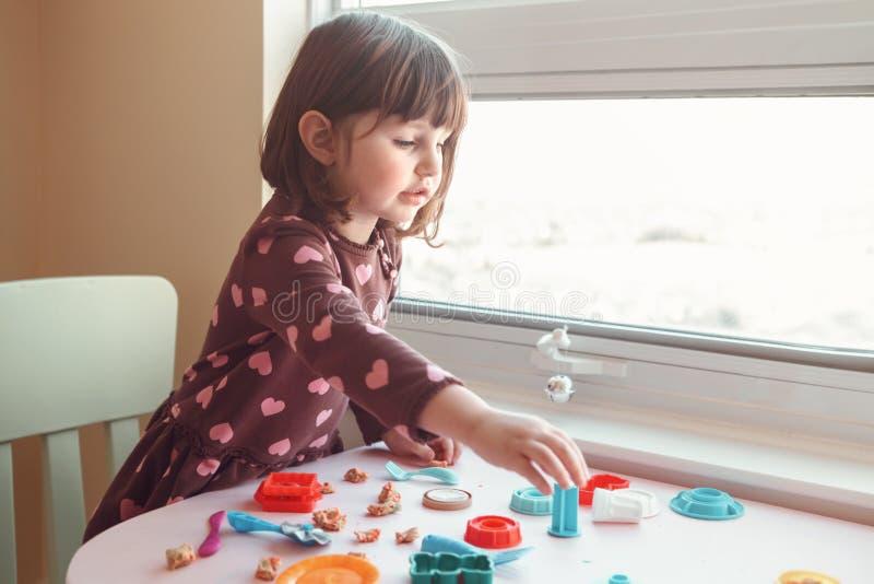 Muchacha caucásica blanca del preescolar que juega el playdough del plasticine dentro en casa fotografía de archivo