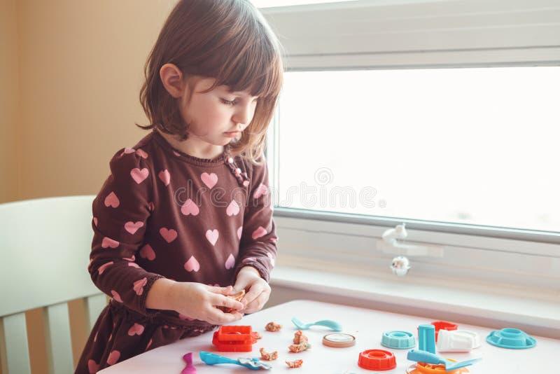 Muchacha caucásica blanca del preescolar que juega el playdough del plasticine dentro en casa foto de archivo
