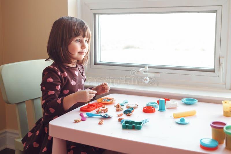 Muchacha caucásica blanca del preescolar que juega el playdough del plasticine dentro en casa foto de archivo libre de regalías