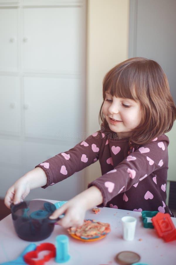 Muchacha caucásica blanca del preescolar que juega el playdough del plasticine dentro en casa imagenes de archivo
