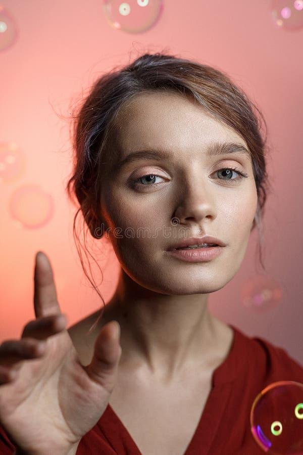 Muchacha caucásica bonita en camisa roja con el escote que mira en cámara en fondo rosado Las burbujas de jabón vuelan alrededor  fotos de archivo