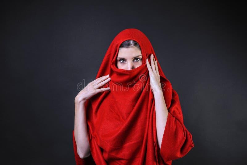 Muchacha caucásica cubierta en un poncho rojo fotos de archivo libres de regalías