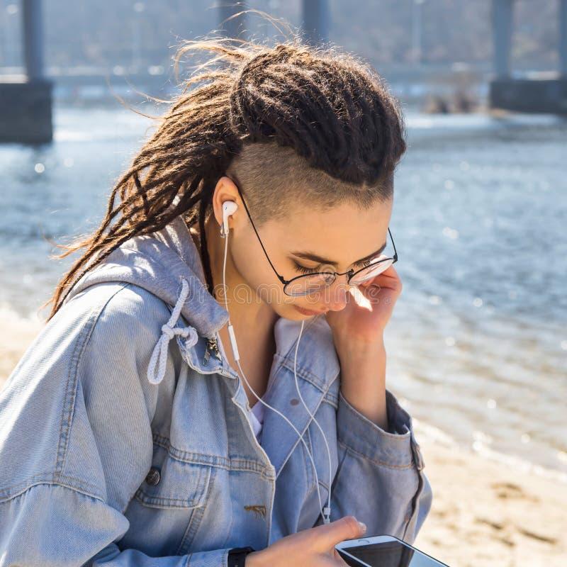 Muchacha caucásica elegante que escucha la música con los auriculares y que descansa en naturaleza en primavera fotos de archivo