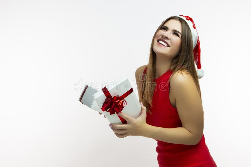 Muchacha caucásica emocionada y sonriente en vestido y Santa Hat rojos Caja de regalo blanca de apertura envuelta para arriba con foto de archivo libre de regalías