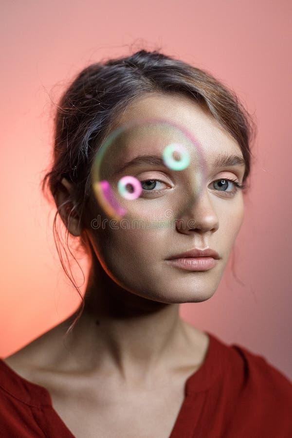 Muchacha caucásica en camisa roja con el escote que mira en cámara en fondo rosado La burbuja de jabón vuela delante de su ojo foto de archivo