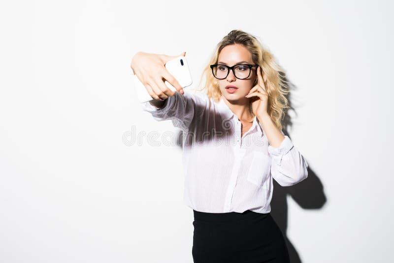 Muchacha caucásica feliz que habla vía Internet Teléfono celular bonito joven de tenencia de la mujer que hace la llamada y el ge foto de archivo libre de regalías