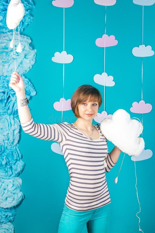 Muchacha caucásica hermosa y joven que sostiene las nubes suaves blancas en fondo azul imagen de archivo libre de regalías