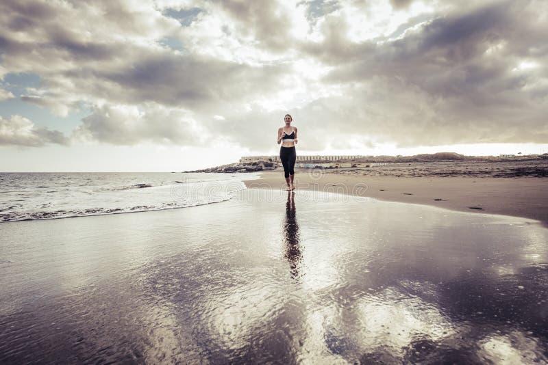 Muchacha caucásica joven de la señora sola del corredor en la playa en el estilo descalzo que corre en la orilla ondas y activida fotografía de archivo
