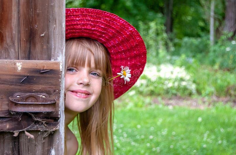 Muchacha caucásica joven que mira a escondidas alrededor de puerta imagen de archivo libre de regalías