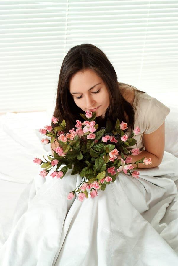 Muchacha caucásica joven que se sienta en cama con las flores imagen de archivo