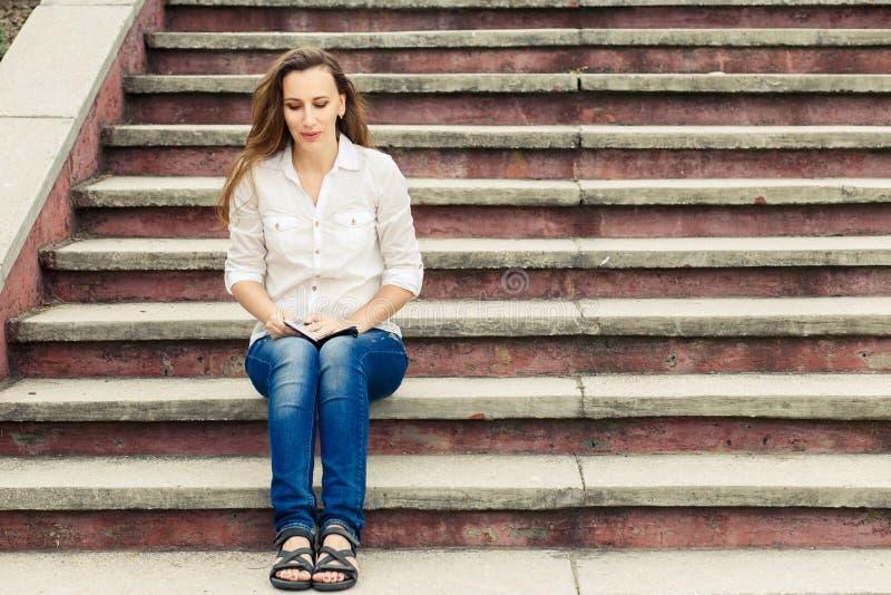 Muchacha caucásica joven que se sienta en las escaleras con la nota fotos de archivo