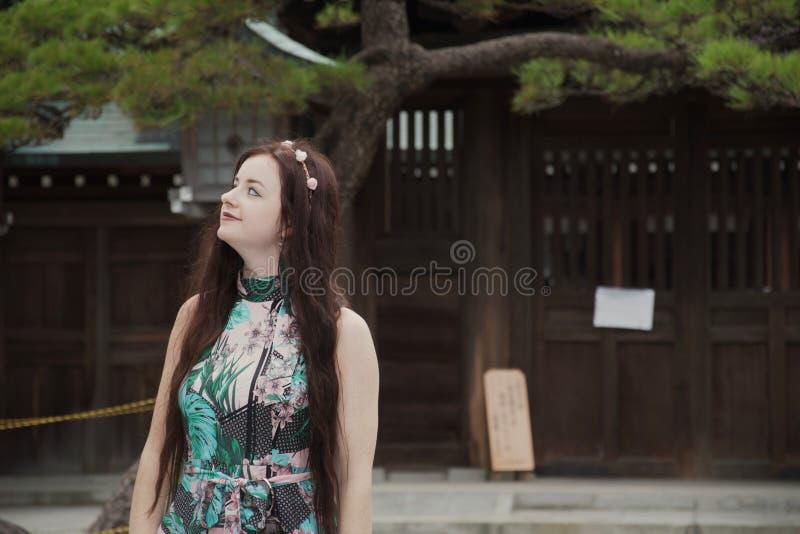Muchacha caucásica morena del hippie que sonríe en patio japonés imagen de archivo