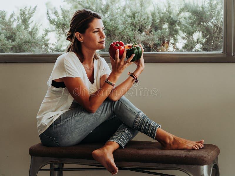 Muchacha caucásica que se sienta en su cocina que muestra tres pimientas coloreadas grandes Verde, rojo y amarillo fotografía de archivo