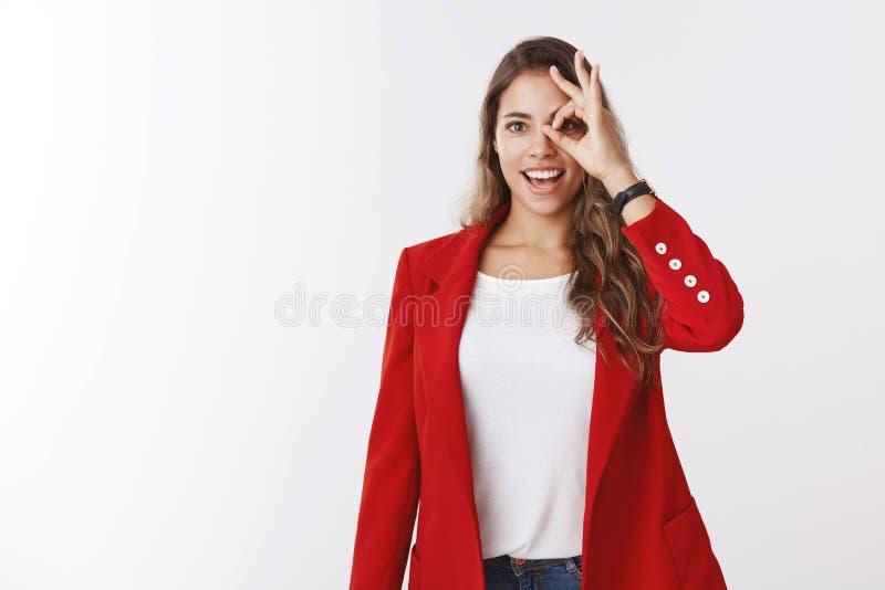 Muchacha caucásica rizado-cabelluda magnífica soñadora entusiasta divertida que lleva la chaqueta roja que mira con el gesto de l foto de archivo libre de regalías