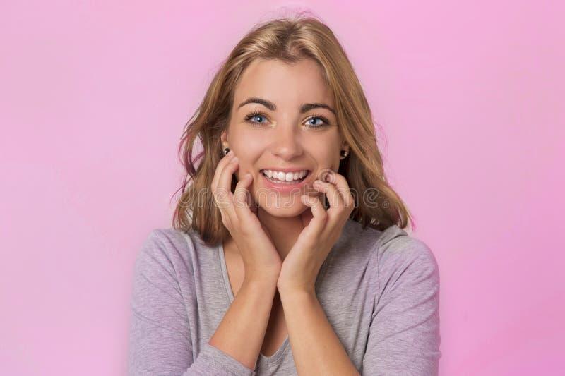 Muchacha caucásica rubia bonita y atractiva con los ojos azules hermosos en su 20s emocionado y la sonrisa feliz alegre en cara d imagenes de archivo