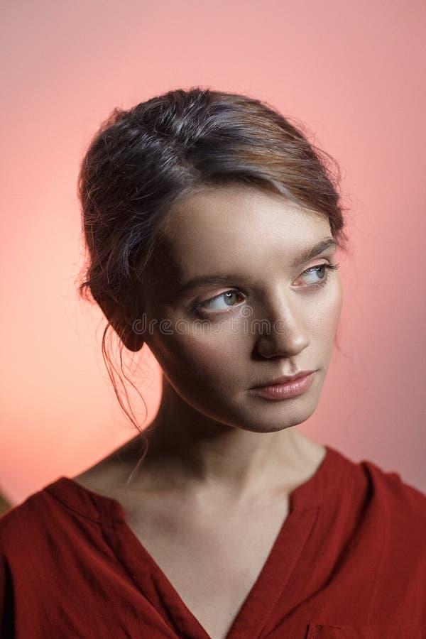 Muchacha caucásica sensual atractiva en la camisa roja que mira lejos y que inclina su cabeza Retrato de la belleza en fondo rosa imagenes de archivo